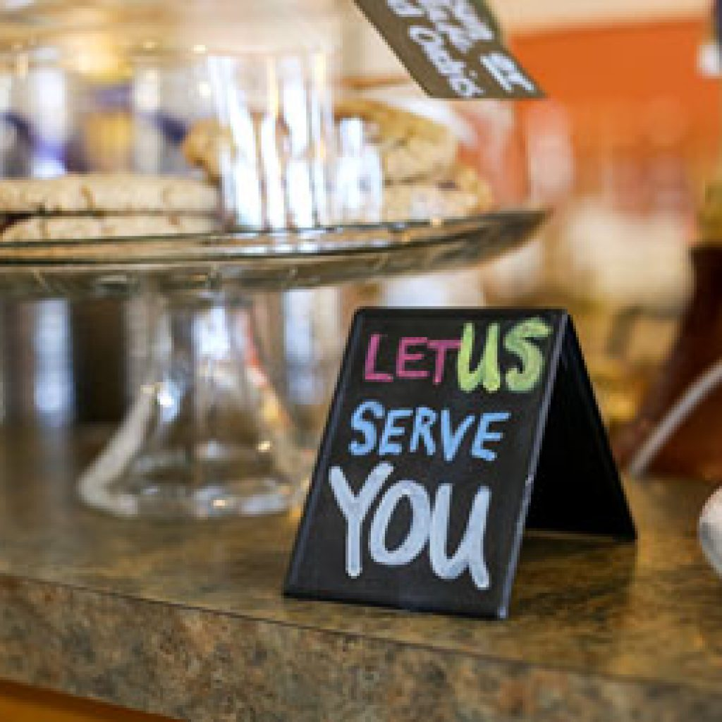 Let Us Serve You card in front of a dessert tray.