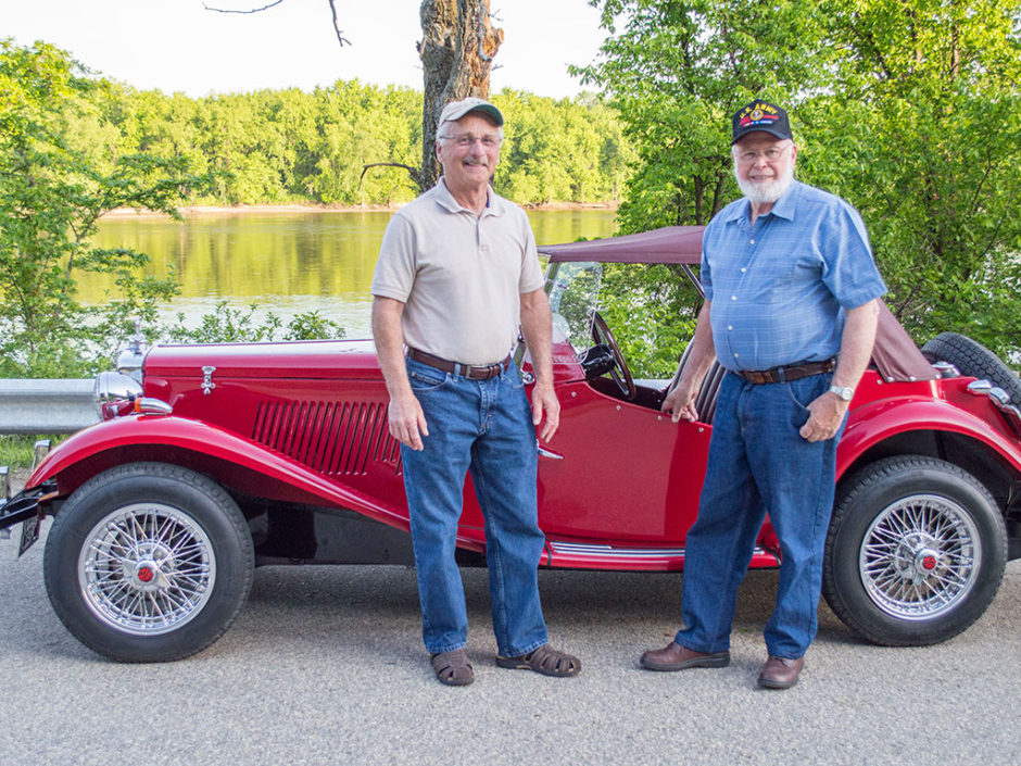 A photo of two men in front of an old red Rolls Royce.