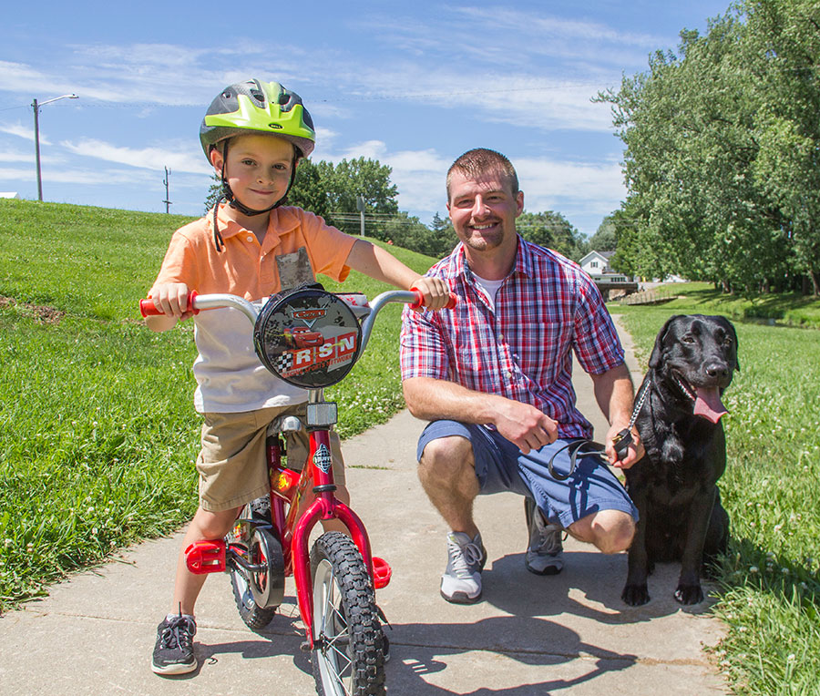 A photo of a man, a dog, and a young boy on a bike.