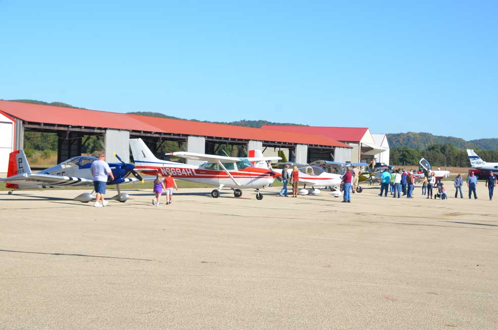 People and airplanes in front of the hangars.