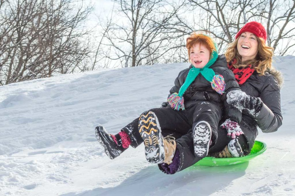 A woman and young child sledding.