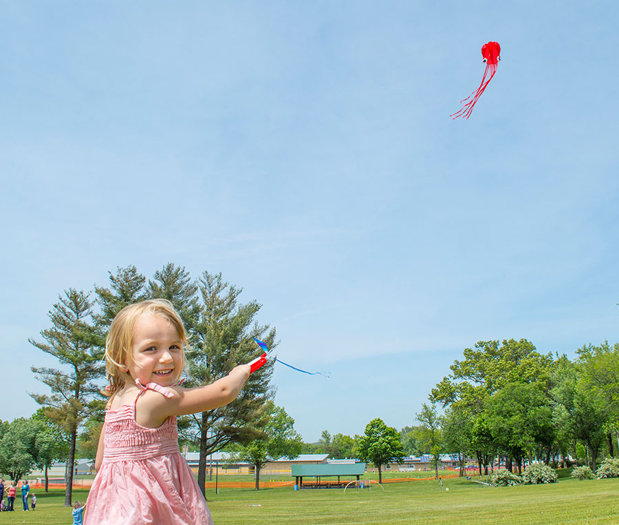A photo of a little girl flying a red kite.